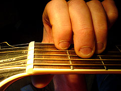 Someone who bites their fingernails playing an 'A Minor' Guitar chord